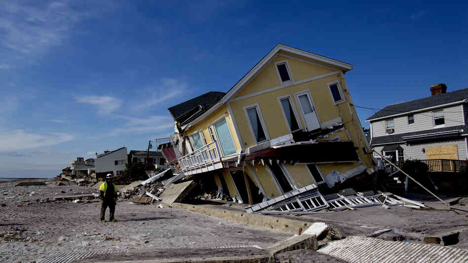 A damaged home rests on one side along the beach in the Belle Harbor section of Queens, N