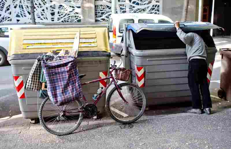 A man searches through trash bins in Girona, Spain. Across Spain, people are increasingly dumpster diving for scraps of food or metal.