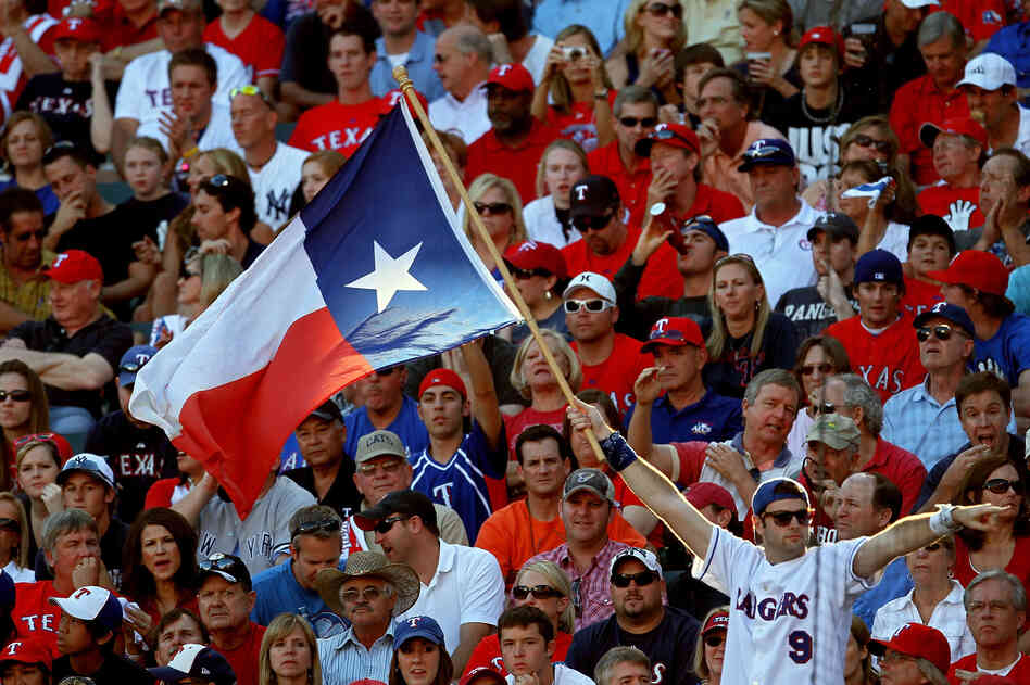 A fan holds up the Texas state flag during Gam