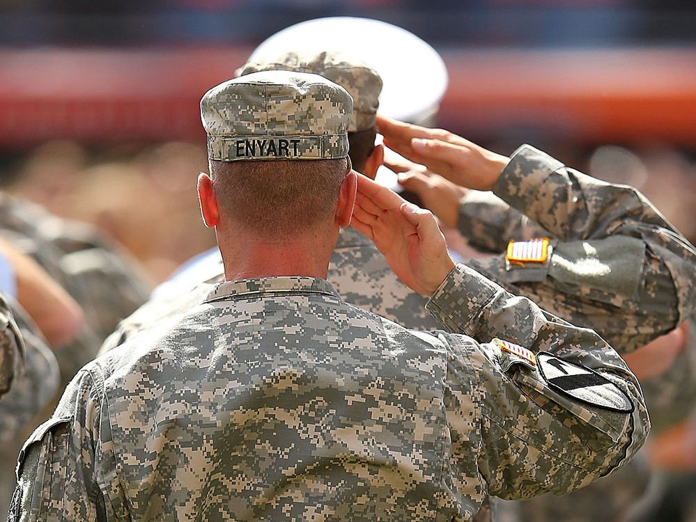 Major Ehyart of the US Army salutes during the national anthem during a game between the Miami Dolphins and the Tennessee Titans at Sun Life Stadium on November 11, 2012 in Miami Gardens, Florida.