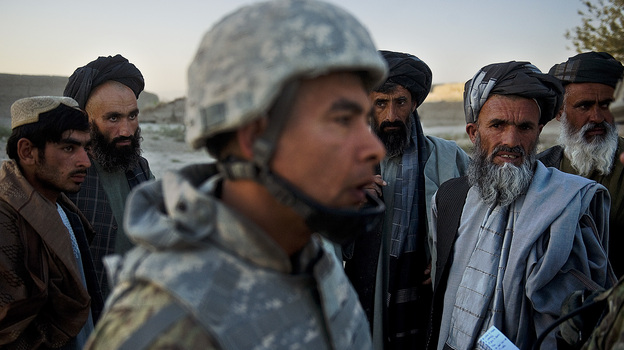 Afghan villagers look at a translator as U.S. soldiers tend to an injured local Afghan man, who was shot for being suspected of planting a roadside bomb in Genrandai village at Panjwai district, Kandahar, on Sept. 24. (AFP/Getty Images)