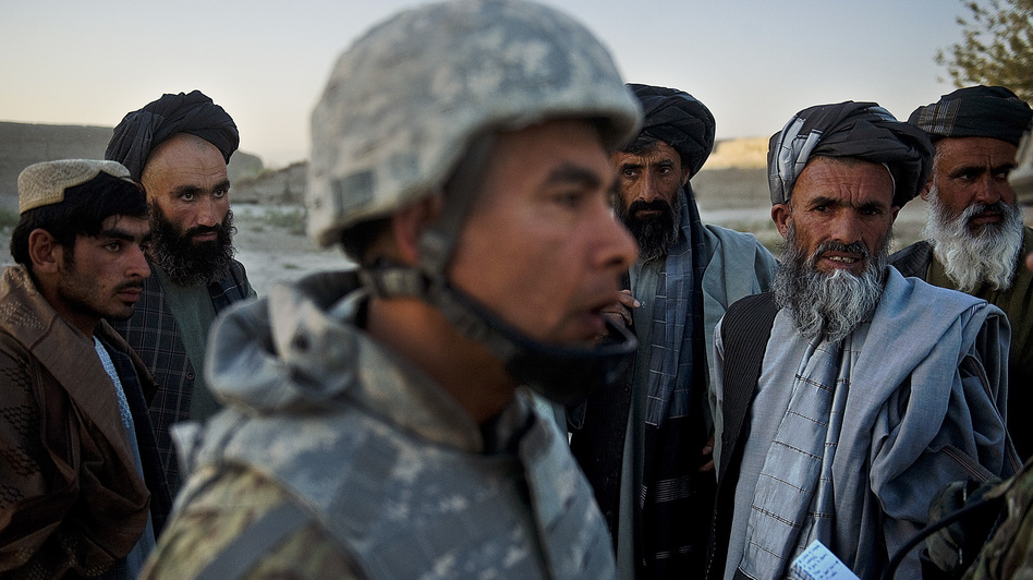 Afghan villagers look at a translator as U.S. soldiers tend to an injured local Afghan man, who was shot for being suspected of planting a roadside bomb in Genrandai village at Panjwai district, Kandahar, on Sept. 24.