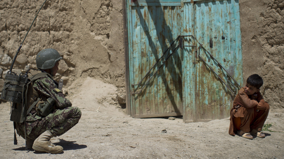 An Afghan boy watches an Afghan National Army soldier on patrol in Logar province, eastern Afghanistan, on May 17. NATO forces are scheduled to leave Afgahnistan by the end of 2014. (AP)