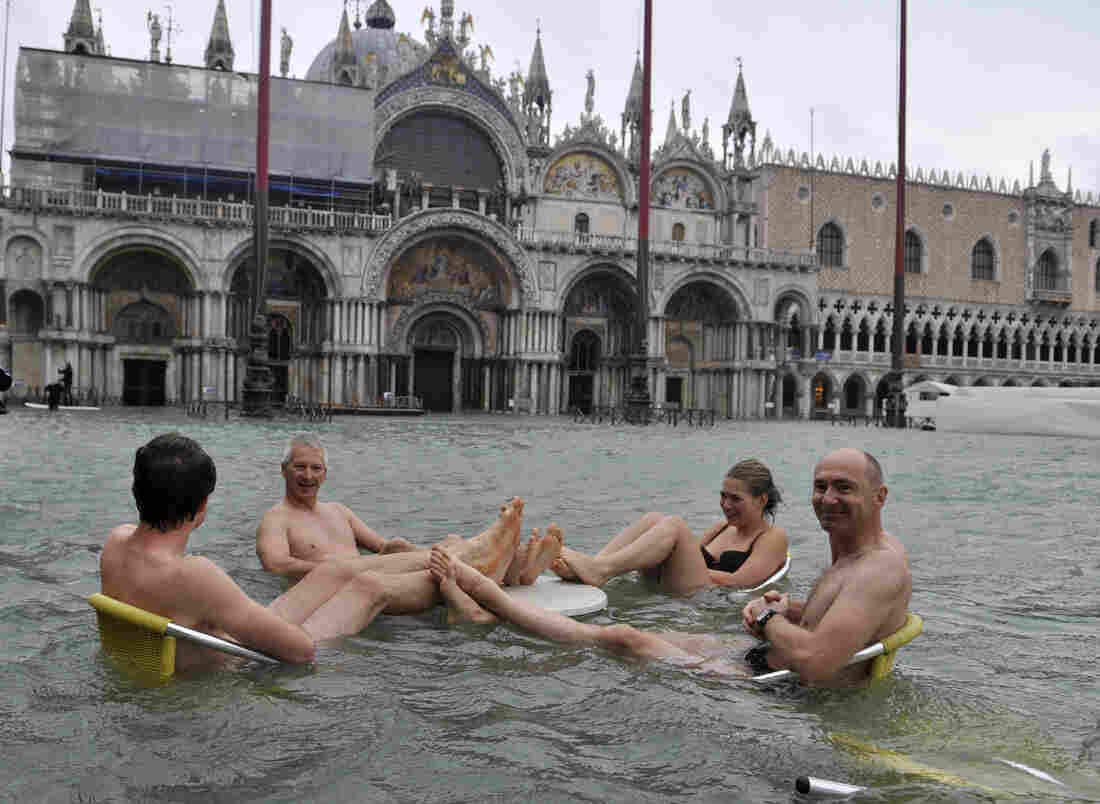 People sit at the table of a bar in a flooded St. Mark's Square in Venice, Italy on Sunday.