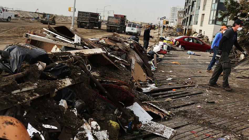 Volunteers help to clean up in the heavily damaged Rockaway neighborhood where a large section of the iconic boardwalk was washed away. (Getty Images)