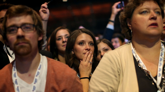 Spectators react to Mitt Romney's concession speech early Nov. 7 in Boston. President Obama won virtually every swing state and comfortably won the electoral vote despite some polls projecting a Romney victory. (Getty Images)