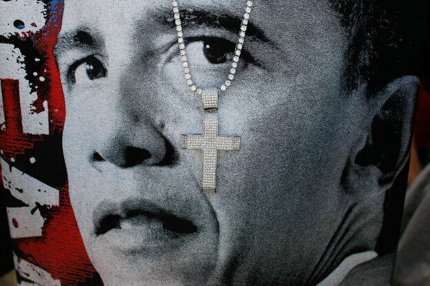 A cross hangs in front of a T-shirt printed with Barack Obama's face at a 2008 campaign event in Las Vegas.