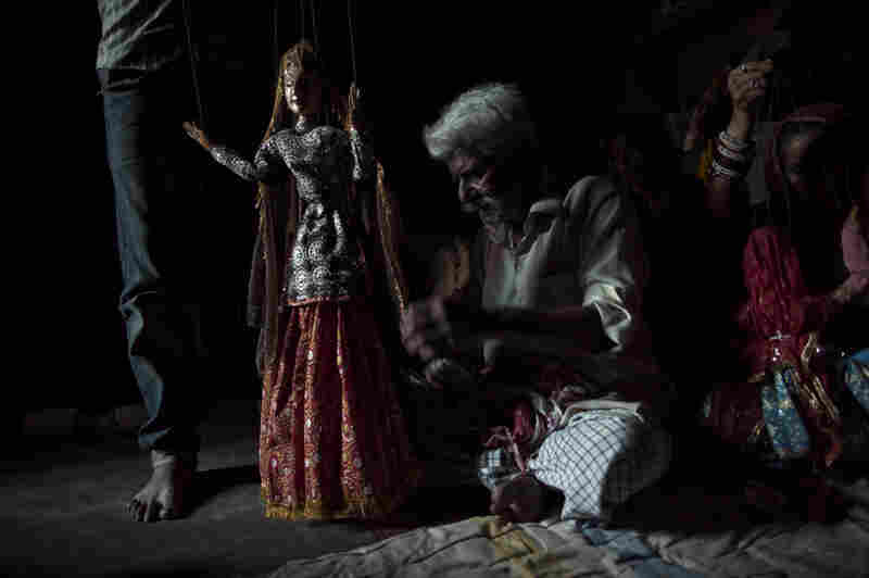 One-Eyed Bhatt is one of the few remaining master puppeteers. Here he readies one of his puppets for performance, unraveling some of the 18 strings that are used to bring the figures to life. One-Eyed Bhatt is the oldest puppeteer remaining in Kathputli. He spent his childhood as an itinerant performer, playing music, puppeteering and telling mythic tales in small villages.