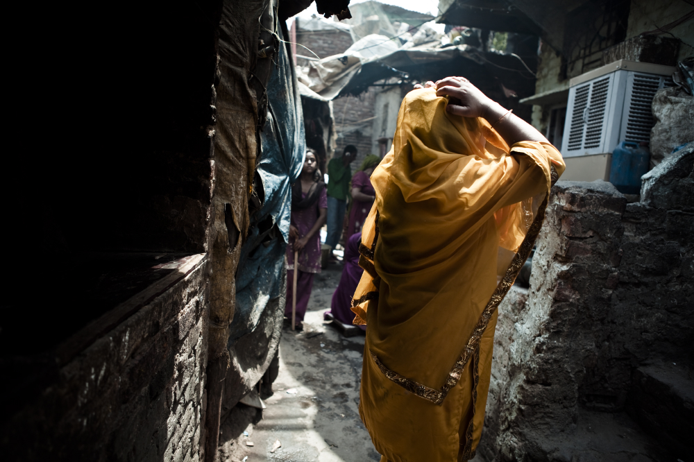 A woman adjusts her sari in the colony's tight alleys.