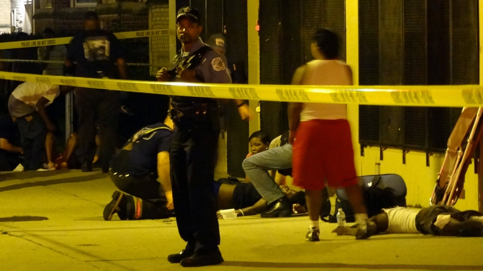 Paramedics treat multiple gunshot victims in Chicago in August. (MCT/Landov)