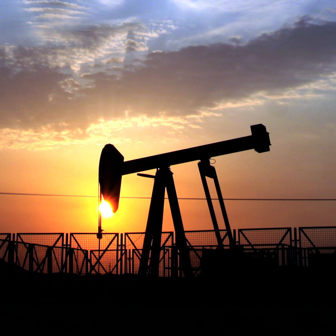 An oil pump operates in the desert oil fields of Sakhir, Bahrain, at sunset on Oct. 29, 2012.