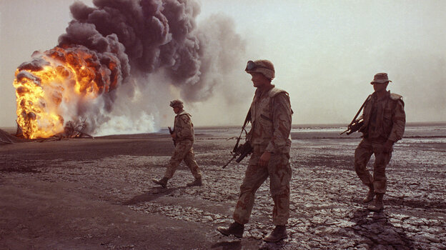 A U.S. Marine patrol walks across the charred oil landscape near a burning well near Kuwait City in March 1991. Concerns about oil supply were at play when the U