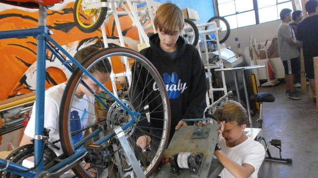 Students Blake Jamar (from left), Ryan Clifton and Gregory Gonzales take apart a bicycle that generates electricity at Analy High School in Sebastopol, Calif. (Jon Kalish for NPR)