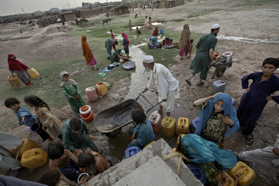 Afghan refugees collect water from a water point in a slum area on the outskirts of Islamabad, in May. (AP)