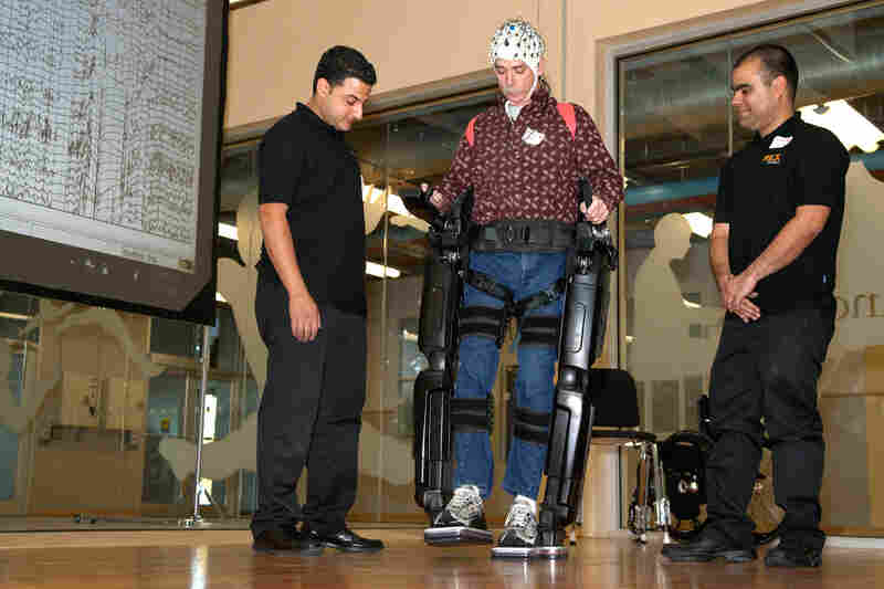 Steve Holbert (center), a paraplegic, demonstrates NeuroRex, a bionic exoskeleton suit augmented with a neural interface cap, developed by researchers at the University of Houston. Holbert controlled the robot's movements with his thoughts.