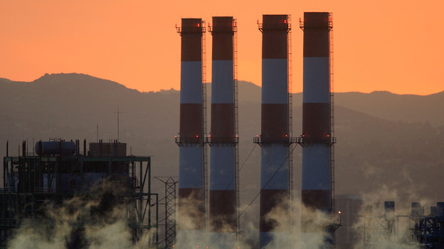 California begins a new plan to ration greenhouse gas emissions from large companies on Wednesday. Big companies must limit the greenhouse gases they emit and get permits for those emissions. Above, the Department of Water and Power San Fernando Valley Generating Station, in Sun Valley, Calif., in 2008. (Getty Images)