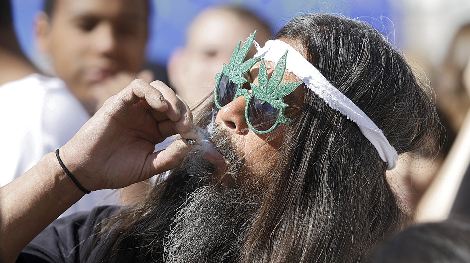 Fast Eddy Aki'a of Hawaii smokes a joint as thousands of supporters of legalized pot, lit up at 4:20 p.m. on April 20 in Denver, Colorado. (Getty Images)