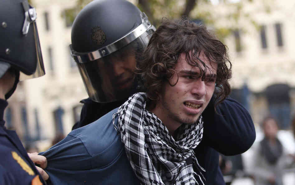 Riot policemen arrest a protester in Valencia on Wednesday during a general strike.