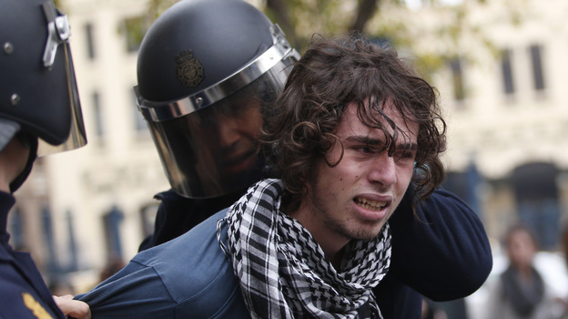 Riot policemen arrest a protester in Valencia on Wednesday during a general strike . (AFP/Getty Images)