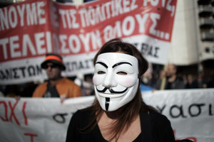A protester with a mask marches during an anti-austerity protest in Athens, Greece.