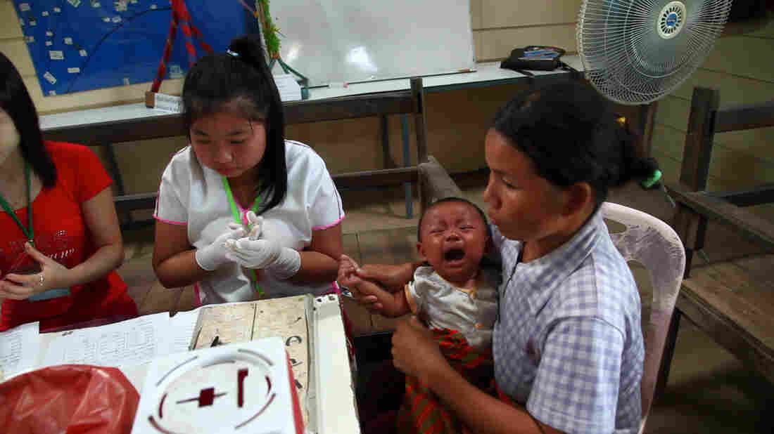 Health workers take a blood sample from an infant to test for the malaria at a clinic along the border between Thailand and Myanmar.