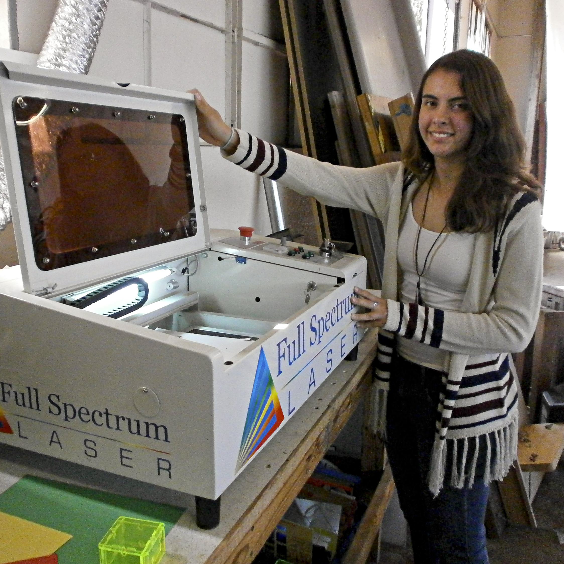 Jessie Davidson shows the school's laser cutter, which is used to burn the school insignia onto plastic objects, among other things.
