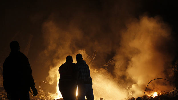 Palestinians try to extinguish fire following an Israeli air strike on Wednesday in Gaza City. (AFP/Getty Images)