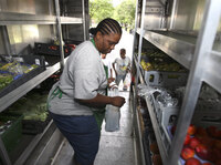 Peaches & Greens driver Diane Brown helps customers out of her truck in Detroit where she sells fresh fruits and vegetables.