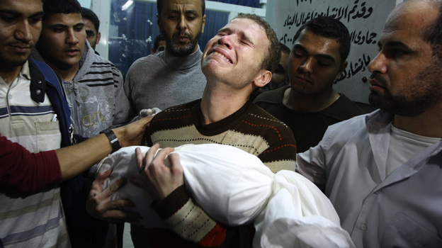 Jihad Masharawi weeps while he holds the body of his 11-month old son Ahmad, at Shifa hospital following an Israeli air strike on their family house, in Gaza City on Wednesday. (AP)