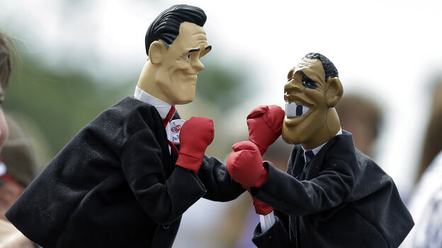 Lynn Armstrong Coffin and Eric Papalini box with puppets depicting Mitt Romney and President Obama in Sarasota, Fla., in September.