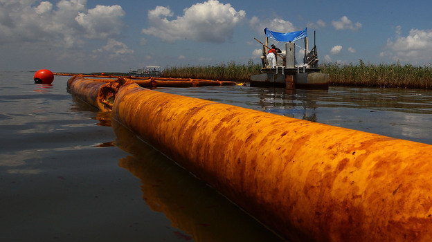 June 2010: A boom floats in the water as contract workers from BP use skimmers to clean oil from a marsh near Venice, La. (Getty Images)