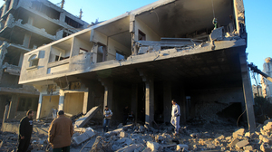Palestinians inspect a destroyed building in an area targeted by an Israeli air strike in Gaza City earlier today.