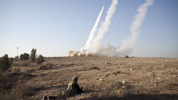 An Israeli soldier lies on the ground as missiles are fired from an Iron Dome anti-missile station on Thursday near the city of Beer Sheva, Israel. The Iron Dome was activated to intercept incoming rockets launched from Gaza.