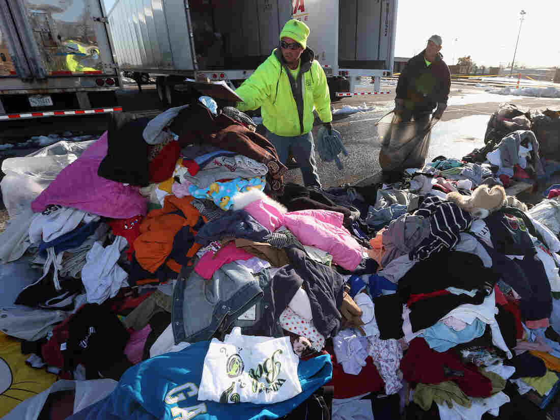 James Vouloukos (left) and William Ferris sort through donated clothes in Oceanside, N.Y. Relief workers say cash is more useful than donated supplies for their efforts.
