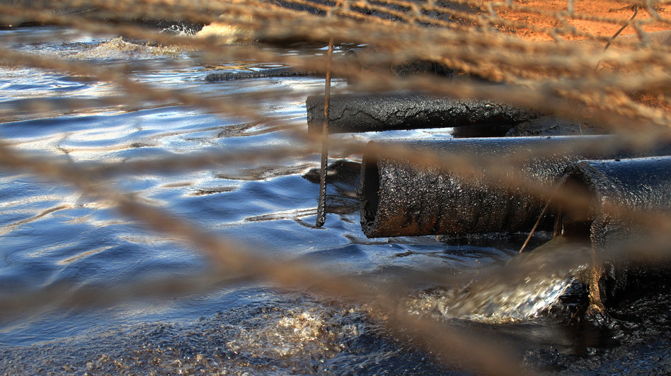Dirty water from the oil wells flows through oil-caked pipes into a settling pit where trucks vacuum off the oil. A net covers the pit to keep out birds and other wildlife. Streams of this wastewater flow through the reservation and join natural creeks and rivers. (NPR)