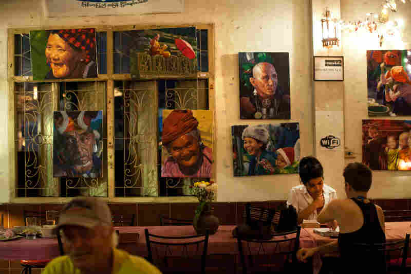 """Paintings of Burmese street scenes decorate the walls of Aiya. Patrons who come for the Burmese and Thai food can also find portraits of Che Guevara and Aung San Suu Kyi, and bumper stickers declaring """"Peace in Burma Now."""""""