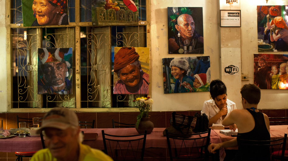"Paintings of Burmese street scenes decorate the walls of Aiya. Patrons who come for the Burmese and Thai food can also find portraits of Che Guevara and Aung San Suu Kyi, and bumper stickers declaring ""Peace in Burma Now."" (NPR)"