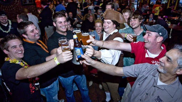 Not surprisingly, men like these guys cheering Sam Adams love beer. But more women than you might expect do too, according to a new study. (AP)