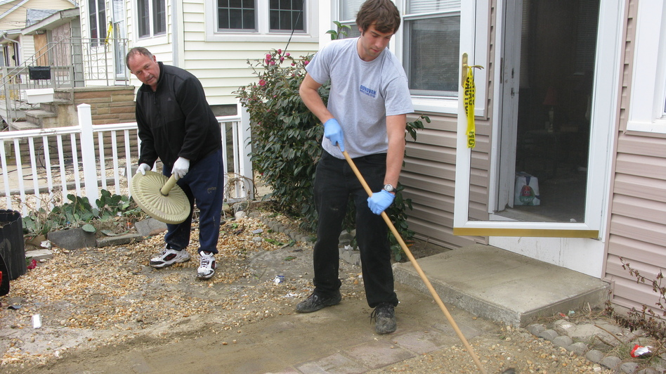 Wayne Duszczak (left) and his son Anthony clean up the gravel yard of their Seaside Heights home, which was badly damaged during Superstorm Sandy. (NPR)