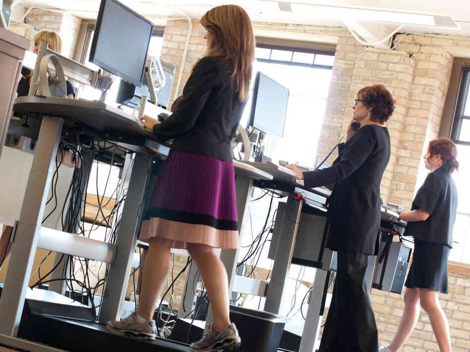 Employees at at Salo, a Minneapolis-based financial consulting firm, walk while working on treadmill desks. The firm offers treadmill desks for employee use and encourages an active workplace environment.