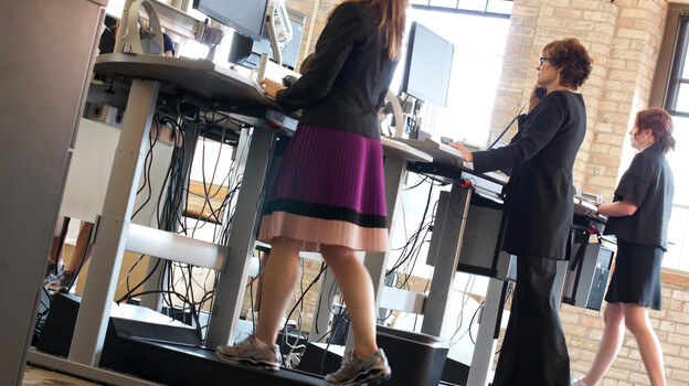 Employees at at Salo, a Minneapolis-based financial consulting firm, walk while working on treadmill desks. The firm offers treadmill desks for employee use and encourages an active workplace environment. (Salo LLC)