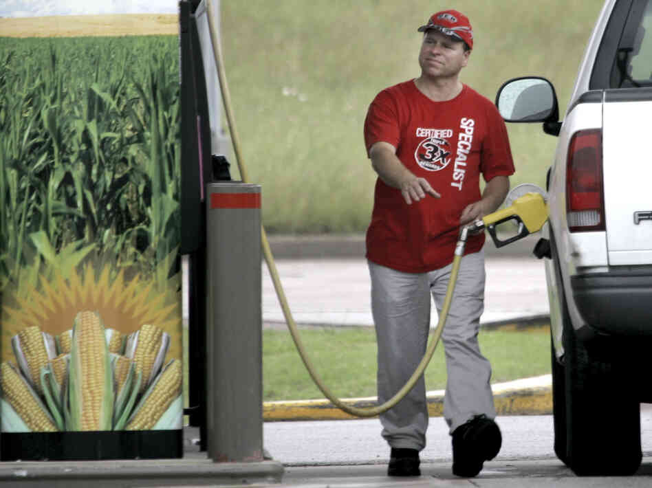 A sign on the pump advertises the ethanol content of the gasoline as a motorist reaches for