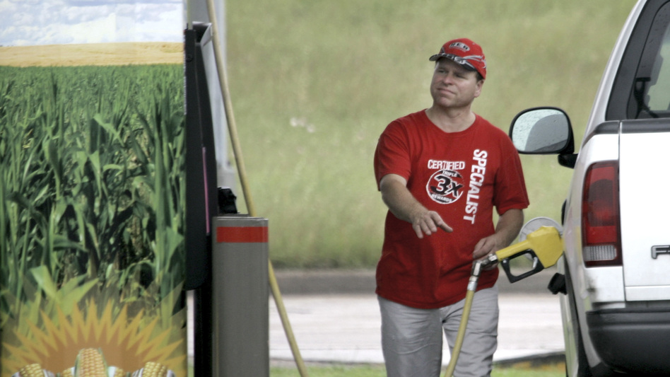 A sign on the pump advertises the ethanol content of the gasoline as a motorist reaches for the gas pump in his truck at a filling station in Bellmead, Texas. (AP)