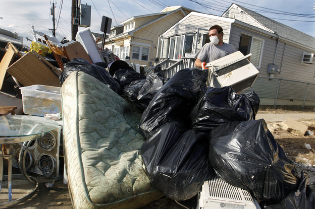 Ernest Shallo, of Carteret, N.J., throws a ruined air conditioner onto a pile of debris in front of a small home in Seaside Heights,