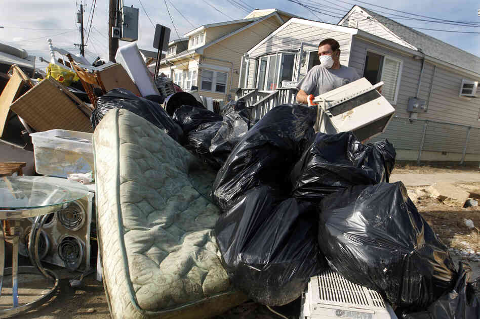 Ernest Shallo, of Carteret, N.J., throws a ruined air conditioner onto a pile of debris in front of a small home in Seaside Heights, N.J. Resid