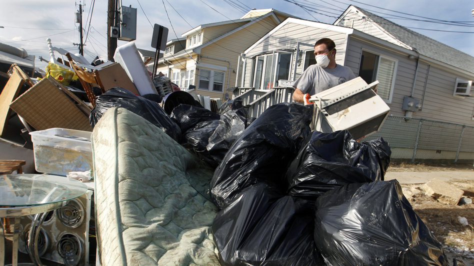 Ernest Shallo, of Carteret, N.J., throws a ruined air conditioner onto a pile of debris in front of a small home in Seaside Heights, N.J. Residents were allowed back in their homes for a few hours Monday, two weeks after the region was pounded by Superstorm Sandy. (AP)