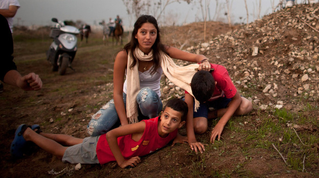 Israeli civilians in Tel Aviv run for cover during a rocket attack launched from Gaza on Saturday. (Getty Images)