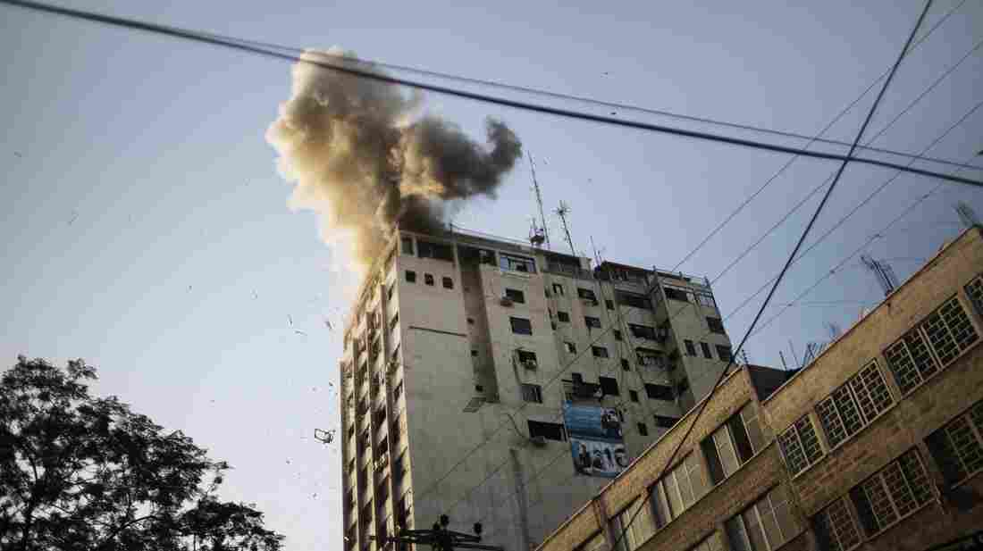 Smoke billows from the local Al-Aqsa TV station in Gaza City Sunday after an Israeli airstrike.