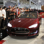 Tesla workers cheer on the first Tesla Model S cars sold during a rally at the Tesla factory in Fremont, Calif., in June.