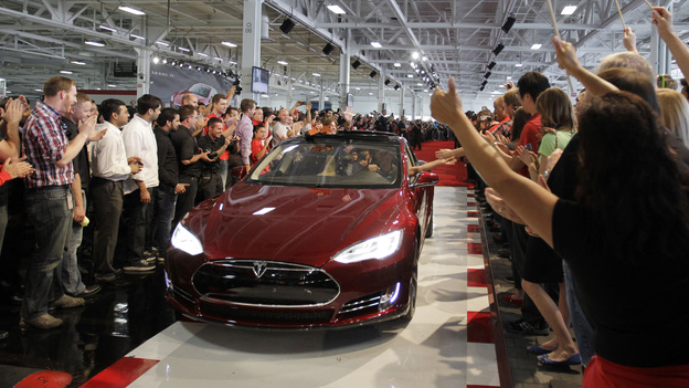 Tesla workers cheer on the first Tesla Model S cars sold during a rally at the Tesla factory in Fremont, Calif., in June. (AP)